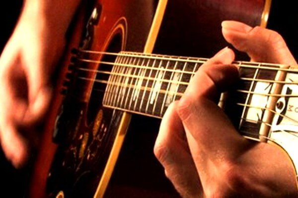 Close up shot of guitarist playing acoustic guitar.