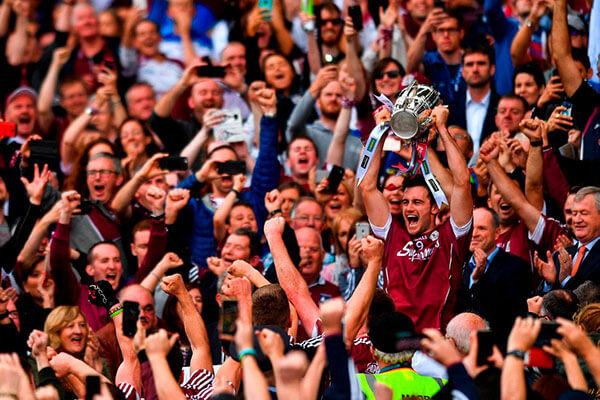 David Burke lifts the Liam McCarthy Cup in Croke Park surrounded by fans.